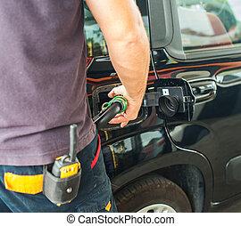Man fills the car at gas station.