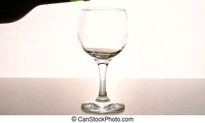 Man fills transparent glass with red wine in restaurant...