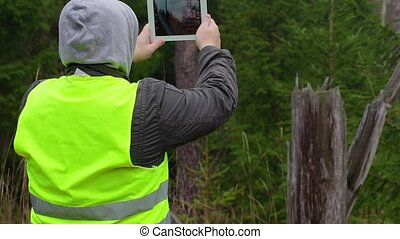 Man filmed with tablet PC in forest