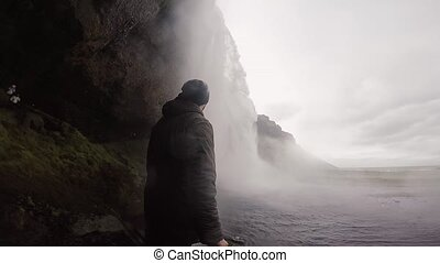 Man filming on gopro camera the beautiful and powerful Seljalandsfoss waterfall in Iceland. Water splashing on the rocks