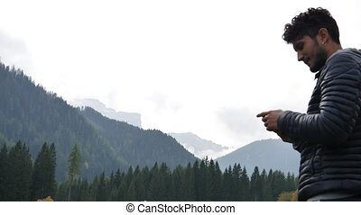 Man filming video of cows in the mountain