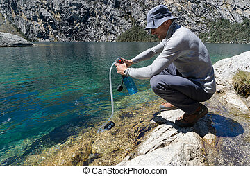 Man drinking water from a hand hole of lake  Man drinking