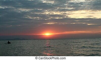 man find seafood in the sea when sunset
