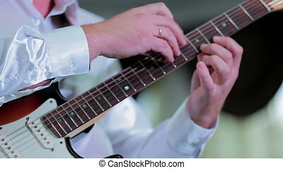 man fingering the fretboard guitar