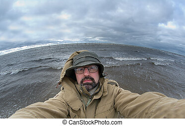 man-fisherman on background Big ocean wave