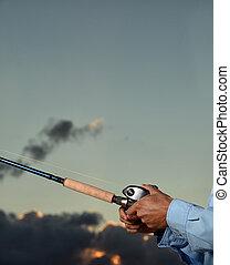 Man fishing during sunrise