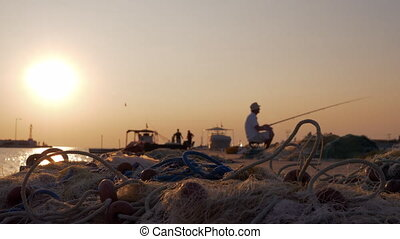 Man fishing from the pier in harbor at sunset