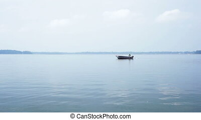 Man fishing in a boat on a lake.