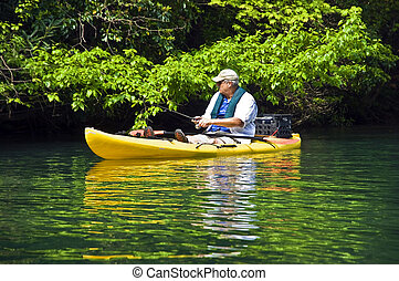 Man Fishing in Kayak - A man in a kayak at the shore fishing...