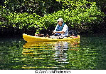 Man Fishing in Kayak - A man in a kayak at the shore...