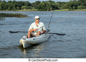 Man enjoys fishing from kayak on a beautiful day at dusk.