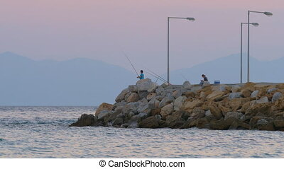 Man fishing in the sea from rocky pier, evening scene