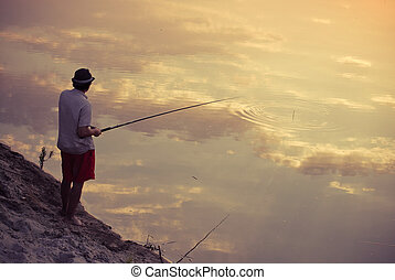 Man fishing in the sky reflection in sunset