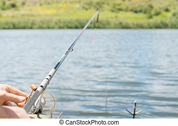 Man fishing on a lake with a spinning reel and rod