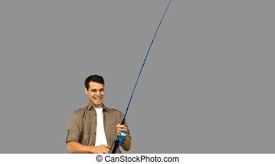 Man fishing on grey screen in slow motion