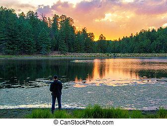 Man Fishing on Lake Shore at Sunset