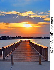 Man fishing from a pier on the Chesapeake Bay Maryland at sunset