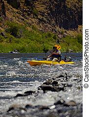 man fishing while paddling a kayak near rapids