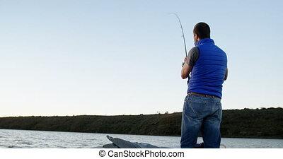Man fishing while standing on motorboat 4k - Man fishing...