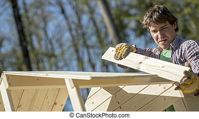 Man fitting a section of wood to an outdoor hut