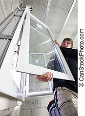 Man fitting a window