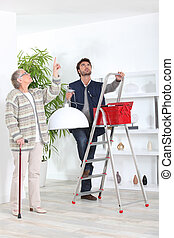 Man fitting ceiling light for old lady