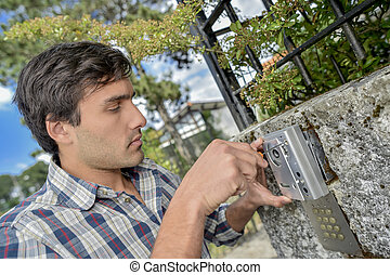 Man fitting electronic security device to exterior wall