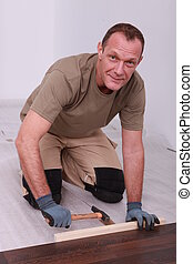 Man fitting laminate flooring