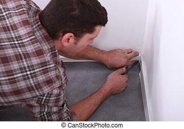 Man fitting linoleum flooring into a corner