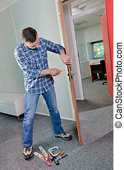 Man fitting lock to interior door