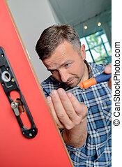 Man fitting new lock to door