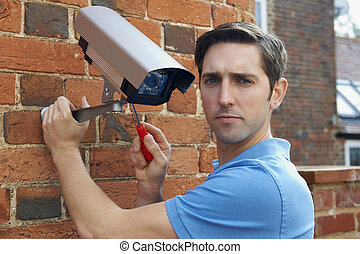 Man Fitting Security Camera To House