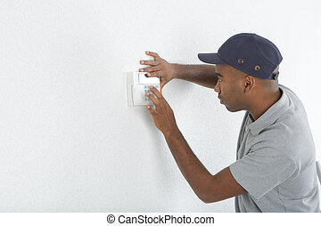Man fitting switch to wall