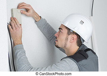 Man fitting thermostat controller to wall