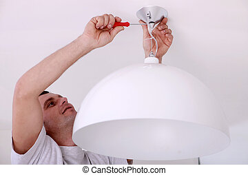 Man fixing ceiling light