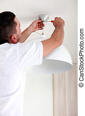 Man fixing ceiling light