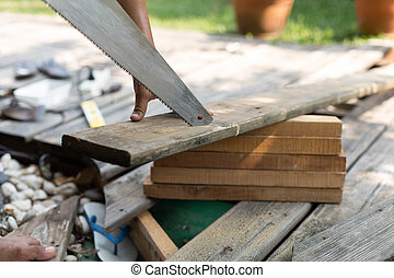 Man fixing decking by sawing a wood with hand wood saw