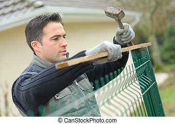 man fixing fence