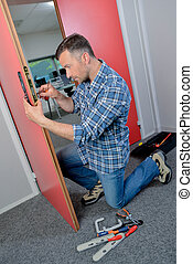 Man fixing lock to a door