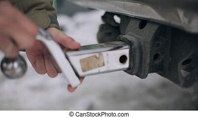 Man fixing new metallic tow hitch to car on street....