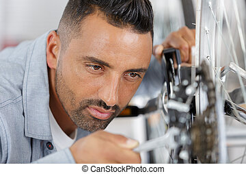man fixing pedals on a bicycle