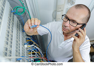 man fixing server network in data center room