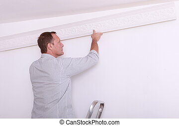 man fixing something on a wall