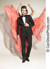 man fixing tuxedo while his lover is fluttering her dress