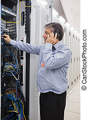Man fixing wires while making a phone call