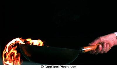 Man flambeing vegetables in pan slow motion on black background