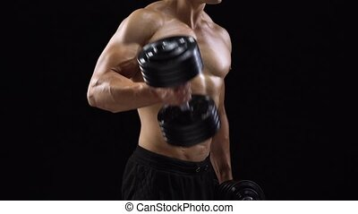 Man flexes his hands with dumbbells, training his biceps on...