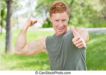 Man flexing and showing thumbs-up sign
