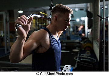 man flexing muscles on cable machine in gym - sport,...