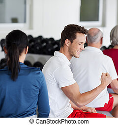 Man Flexing Muscles While Sitting With Family In Gym